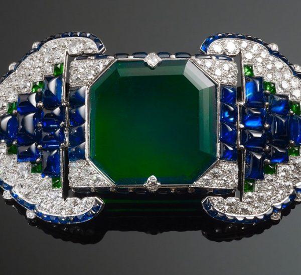 装饰艺术风格祖母绿、蓝宝石和钻石的腰带扣胸针,卡地亚。38.71克拉的八角阶梯形切割祖母绿、圆顶式小型角切割蓝宝石和祖母绿、老式单翻钻、铂金和18K白金(法国标志),3 ½寸,1922年。未签名,制造商部分标记(Atelier Renault),编号:0346,卡地亚红色包装盒