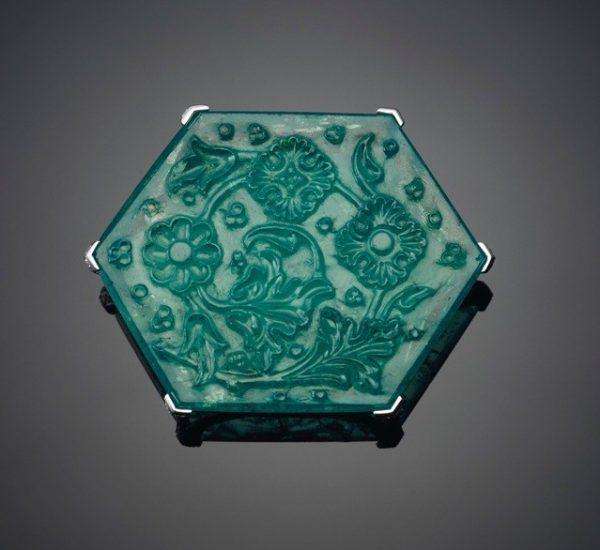 """泰姬陵祖母绿,卡地亚。重达141.13克拉的六角形雕刻片状祖母绿、圆形切割钻石、铂金和18K白金(法国标记)。2⅛英寸,2012年。卡地亚签名,编号:TI9645,上面雕刻有""""Taj Mahal""""(泰姬陵)祖母绿字样的卡地亚红色包装盒"""